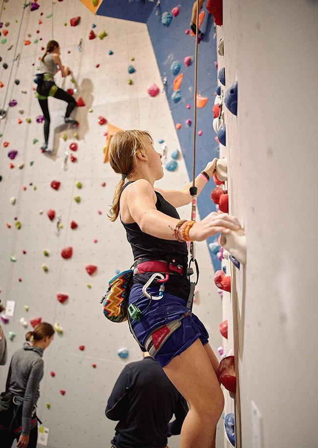 Jonge vrouw klimmen belay veiligheid klimwand